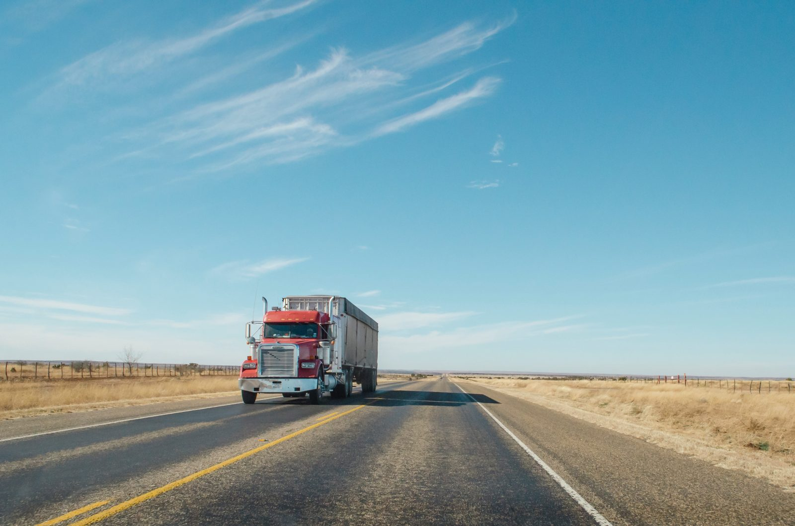 trailer truck passing on road during daytime