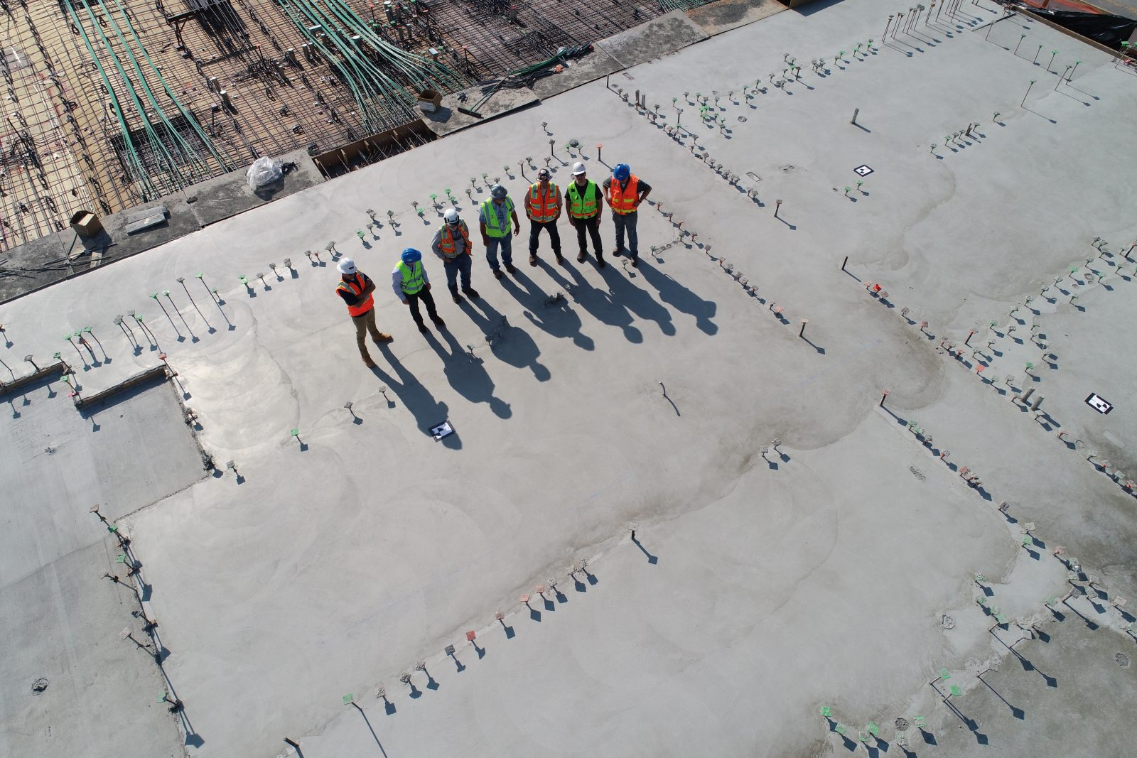 seven construction workers standing on white field
