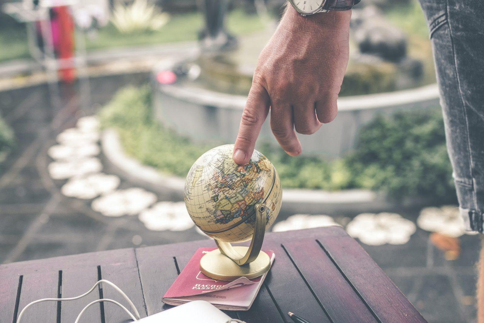 person holding brown desk globe